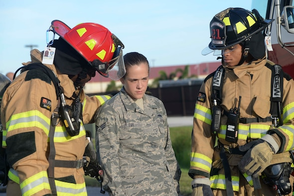Firefighters from the 6th Civil Engineer Squadron escort Senior Airman Sarah Eby, center, Fuels System Repairman apprentice with the 6th Maintenance Squadron, during an Emergency Management exercise at MacDill Air Force Base, Fla., Sept. 13, 2016. Eby acted as an Airman injured from a vehicle accident during the exercise. (U.S. Air Force photo by Senior Airman Vernon L. Fowler Jr.)