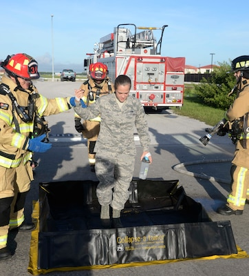 Firefighters from the 6th Civil Engineer Squadron escort Senior Airman Sarah Eby, center, fuels system Repairman apprentice with the 6th Maintenance Squadron, through decontamination during an Emergency Management exercise at MacDill Air Force Base, Fla., Sept. 13, 2016. Eby acted as an Airman injured from a vehicle accident during the exercise. (U.S. Air Force photo by Senior Airman Vernon L. Fowler Jr.)