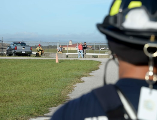 A firefighter from the 6th Civil Engineer Squadron looks on as other firefighters check for environmental damage during an Emergency Management exercise at MacDill Air Force Base, Fla., Sept. 13, 2016. The exercise simulated a fuel spill that resulted from a vehicle accident. (U.S. Air Force photo by Senior Airman Vernon L. Fowler Jr.)
