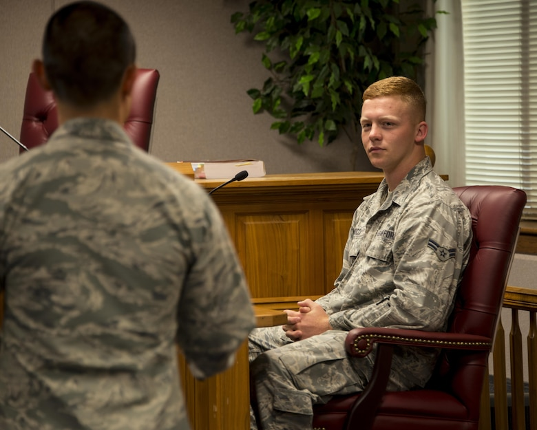 Capt. Joseph Cachuela, 60th Air Mobility Wing Legal Office attorney, left, shows Airman 1st Class Jonathan Rocca, 60th Civil Engineer Squadron electrician, right, what it's like to be on the stand during a court-marital proceeding at Travis Air Force Base, Calif., Sept. 15, 2016. (U.S. Air Force photo by Staff Sgt. Charles Rivezzo)