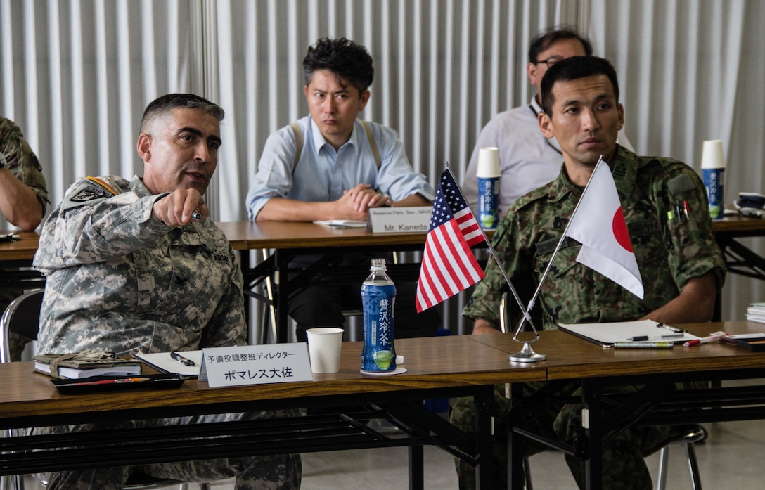 U.S. Army Col. Luis Pomales (center), director, Army Reserve Engagement Team-Japan, explains the U.S. Army Reserve's current challenges and future opportunities in the Pacific with Japan Ground Self-Defense Force Col. Naoki Utimura, chief, Personnel Department, JGSDF Northern Army, during a bilateral Reserve Component conference conducted Sept. 9, 2016, in Camp Sapporo, Japan. Pomales and Utimura shared best practices on how to overcome their respective command's manpower challenges and improve relations between Reserve Component service members and their civilian employers. (Photo by Sgt. John L. Carkeet IV, U.S. Army Japan)