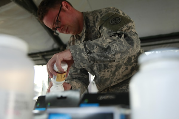 Army Sgt. Frisco Cleary, 396th Combat Support Hospital Company, condenses medications during a medical readiness exercise at San Padro, Guatemala, May 16. As of June, the Medical supply chain's national contracts team has saved $246.4 million through 45 contracts for generic drugs. Photo by Army. Spc. Keslon Brooks