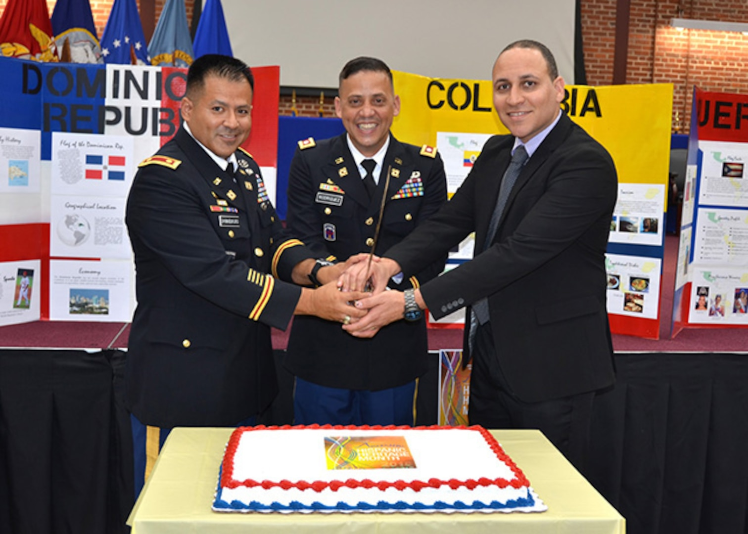 Defense Logistics Agency Aviation's Command Support Directorate and the Equal Employment Opportunity and Diversity Office held a kickoff ceremony for Hispanic Heritage Month on Sept. 16, 2016 in the Lotts Conference Center on Defense Supply Center Richmond, Virginia. Guest speaker Army Lt. Col. Luis Rodriguez, center, Exercise Support Division chief, Logistics Exercise and Simulations Directorate, U.S. Army Training and Doctrine Command from Fort Lee, Virginia, along with DLA Aviation's Army Maj. Alex Shimabukuro, left, operations officer, Customer Operations Directorate and Maurice Sanabria, right, chief, Command Programs Office, Command Support Directorate, prepare to cut the cake.