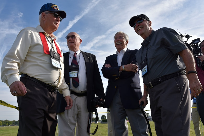 "DAYTON, Ohio -- (From left to right) MSgt.(Ret.) Fred Cook, William Huber, Capt. Randy Harrison and SSgt. Paul Jensen await a CV-22 Osprey fly over before the Green Hornet Dedication ceremony at the National Museum of the United States Air Force, Sept. 15, 2016. These veterans took part in the 26 Nov 1968 mission that is depicted in the National Museum of the U.S. Air Force's UH-1P, 20th SOS ""Green Hornets,"" legacy diorama display. (U.S. Air Force photo by Ken LaRock)"