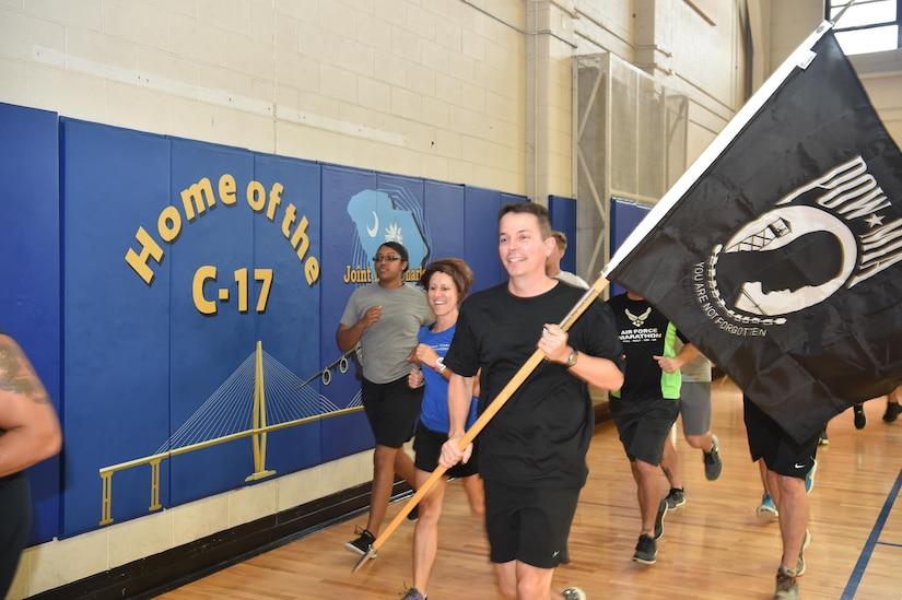 U.S. Air Force Col. Jeffrey Nelson, vice commander of the 437th Airlift Wing, runs the POW/MIA flag at the Air Base fitness center September 15, 2016, at Joint Base Charleston, South Carolina. Every year, members from the base participate in a 24-hour vigil run, a luncheon to honor prisoners of war and those that are missing in action, as well as a formal retreat ceremony.