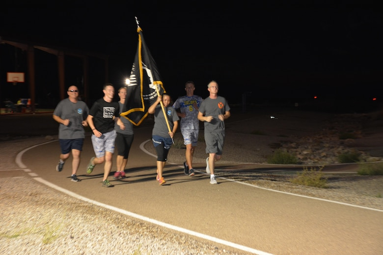 Members of Team Holloman run with the POW/MIA flag during the annual POW/MIA remembrance run at Holloman AFB, N.M., on Sept. 15, 2016. The run, which lasted 24 hours and involved units from all over Holloman, was in remembrance of prisoners of war and those still missing in action. (U.S. Air Force photo by SSgt Warren Spearman)