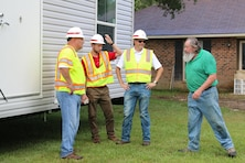 Ron Saunders (L), Brian MacEachern (C) and Mike Barbour (L), quality assurance specialists from the Huntington District, U.S. Army Corps of Engineers talk with a contractor after the delivery of a Mobile Housing Unit to a property owner in Denham Springs, La.