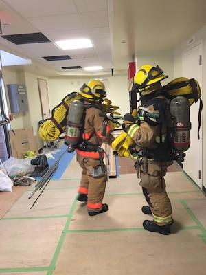 Firefighters with the Marine Corps Installation Pacific Fire and Emergency Services enter a nine story tower on Camp Courtney, Japan with hose packs to distinguish a simulated fire during emergency response training. The tower is one of 14 currently being renovated by the U.S. Army Corps of Engineers, Japan District.