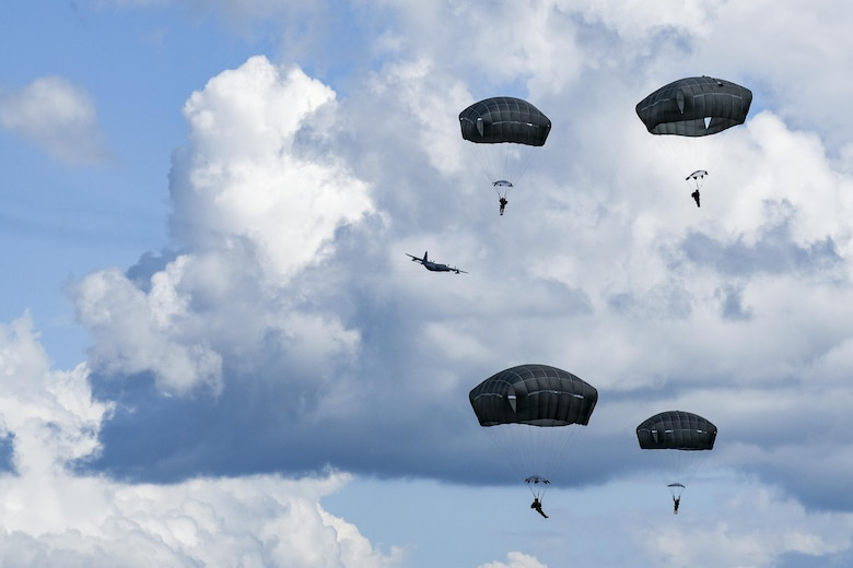 """U.S. Air Force Airmen from the 823d Base Defense Squadron drift during a static-line jump, Sept. 16, 2016, at the Lee Fulp drop zone in Tifton, Ga. In the event that two Airmen collide, they're trained to put their bodies in a """"starfish"""" shape to prevent tangling in each other's parachute. (U.S. Air Force photo by Daniel Snider)"""