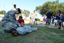 """Jake Pritchard, 20th Security Forces Squadron honorary defender, apprehends a simulated """"suspect"""" during a """"Defender for a Day"""" event at Shaw Air Force Base, S.C., Sept. 9, 2016. Pritchard, who has Duchenne muscular dystrophy, received the opportunity to serve alongside 20th SFS Airmen, as well as learn how to properly apprehend a suspect. (U.S. Air Force photo by Airman 1st Class Christopher Maldonado)"""