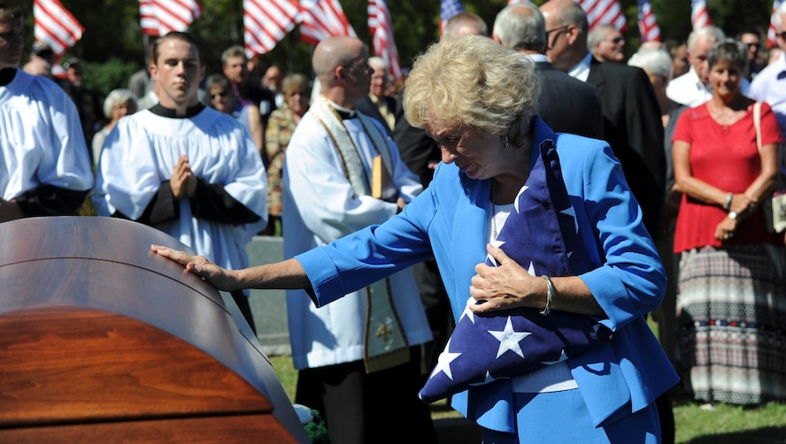 Deanna Klenda, the sister of Maj. Dean Klenda, an F-105 Thunderchief pilot who was listed as missing in action during the Vietnam War, says goodbye to her brother at his funeral, Sept. 17, 2016, at St. John Nepomucene Church in Pilsen, Kan. Klenda was laid to rest exactly 51 years after his aircraft went down in 1965 in North Vietnam. His remains were located and verified by the Defense POW/MIA Accounting Agency. (U.S. Air Force photo/Airman 1st Class Jenna Caldwell)
