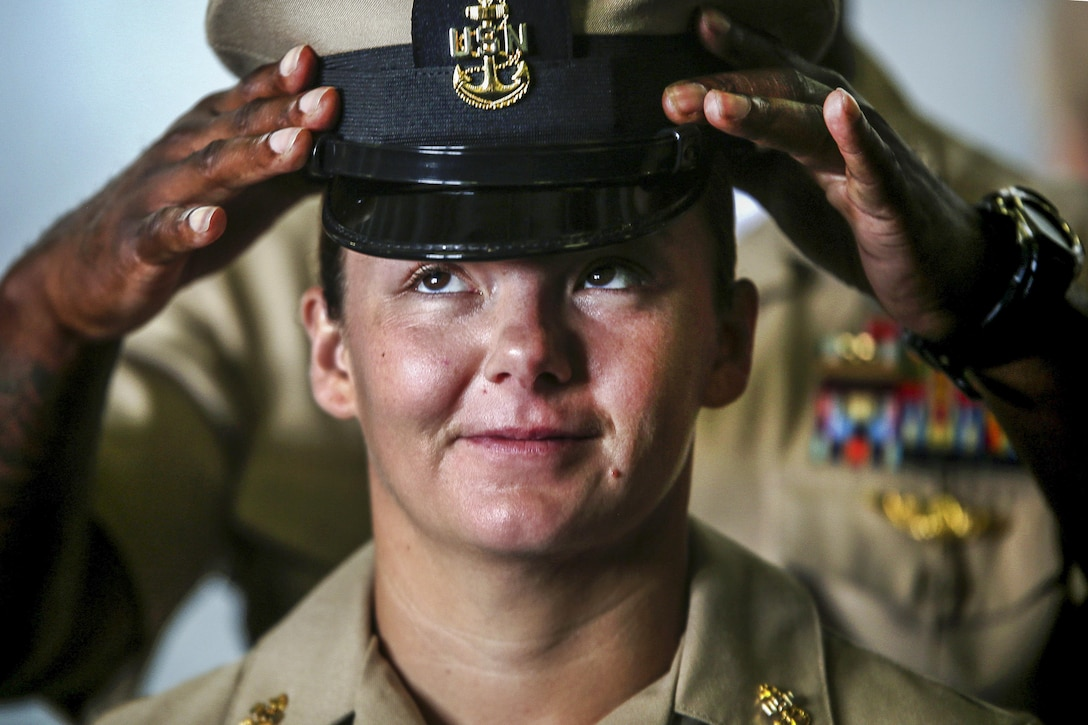 Navy Chief Petty Officer Sarah Powers looks upward as a fellow sailor places a cover atop her head during a ceremony aboard the USS Bataan, Sept. 16, 2016. Donning the cover marks the end of a six-week training season to prepare sailors for the responsibility of the chief. Powers is an aviation boatswain's mate handler. Marine Corps photo by Sgt. Matthew Callahan
