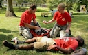 U.S. Air Force Airman 1st Class Anthony Davis, 20th Medical Operations Squadron medical technician and Tech. Sgt. Kathy Cooper, 20th MDOS patient advocate, attend to Airman 1st Class Brandon Hayes, 20th Component Maintenance Squadron electronic warfare systems technician, who simulates having burns on his body during the 1st Annual Medic Games at Shaw Air Force Base, S.C., Sept. 9, 2016. This exercise was a friendly competition between eight medical teams from Shaw AFB and Joint Base Charleston, S.C.   (U.S. Air Force photo by Airman BrieAnna Stillman)