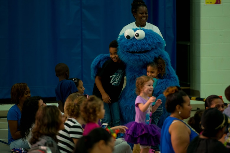 Sesame Street character, Cookie Monster, hugs and takes picture with patrons during the Sesame Street/USO Experience for Military Families tour in the Fort Eustis Youth Center at Joint Base Langley-Eustis, Va., Sept. 16, 2016. The tour is designed to help military families deal with the unique challenges they face, according to USO officials. (U.S. Air Force photo by Staff Sgt. J.D. Strong II)