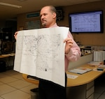 Robert Molleda, a warning coordination meteorologist for the National Weather Service Miami forecast office, holds a weather map while he explains forecasting methods and models used to predict storms at the National Weather Service and the National Hurricane Center Miami, Florida, Sept. 15. The National Weather Service works to provide accurate forecasts and warnings for the protection of life and property, and enhancement of the national economy. (U.S. Air Force photo by Senior Airman Aja Heiden)