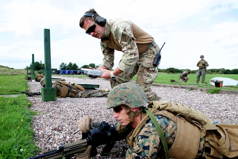 An instructor with the Royal Marines Combat Marksmanship Team tells Sgt. Aaron Meares, a competitor with the Marine Corps Shooting Team, what adjustments need to be made to his SA80 A2 rifle sight, Sept. 11, 2016, at Altcar Training Camp, Merseyside, England. The Marines will be firing these weapons during the Royal Marines Operational Shooting Competition from September 6-22, 2016.  The U.S. Marines are competing against the Royal Netherlands Marine Corps and the Royal Marines. The U.S. Marines are with Weapons Training Battalion, Marine Corps Base Quantico, Virginia.