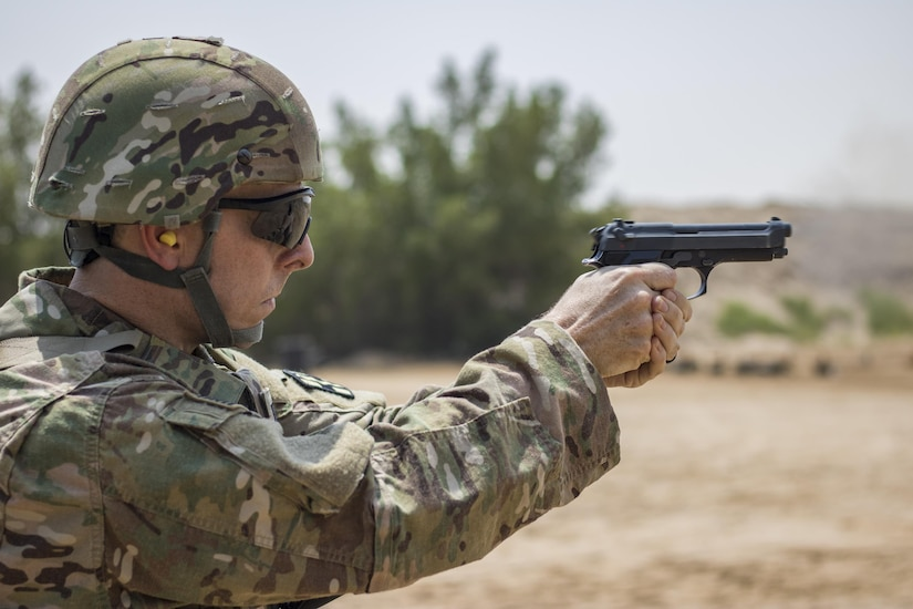 A U.S. Soldier fires at his target during the M9 pistol marksmanship event for a chance to earn his German Armed Forces Proficiency Badge on Aug. 4, 2016 at Camp Arifjan, Kuwait. The marksmanship event was the fourth and last test soldiers had to pass to earn the foreign badge. (U.S. Army photo by Sgt. Angela Lorden)