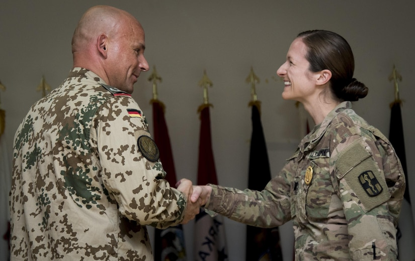 (Right) U.S. Army Capt. Michelle Maust, a psychiatrist for the 10th Combat Support Hospital, is congratulated by (Left) German army Lt. Col. Frank Gillissen for earning a gold German Armed Forces Proficiency Badge on Aug. 5, 2016 at Camp Arifjan, Kuwait. The GAFPB competition, hosted by 10th Combat Support Hospital with the support of German soldiers, consisted of four events that tested soldier speed, agility, strength and endurance. (U.S. Army photo by Sgt. Angela Lorden)