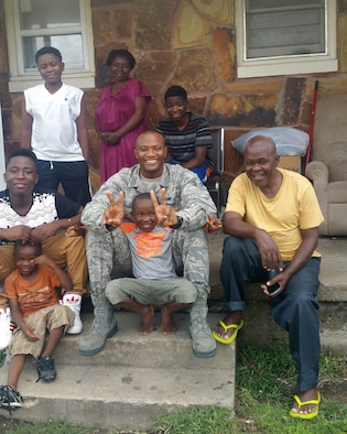 Airman 1st Class Messan Atayi, 22nd Logistics Readiness Squadron mobility Airman, poses for a photo with the Kamoune family in front of their home, Sept. 9, 2016, in Wichita, Kan. The Kamoune Family arrived in the United States in January 2016, as refugees from the Democratic Republic of Congo. (courtesy photo)