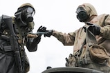 U.S. Army Pfc. Kemper Baker, 4th Battalion, 23rd Infantry Regiment, 2nd Stryker Brigade, 2nd Infantry Division, hands a brush back to a Japan Force Ground Self-Defense member, 3rd Nuclear Biological Chemical unit, 3rd Div., 36th Inf. Reg at Aibano Training Area, Japan, Sept. 15, 2016. The Infantrymen go through the Japanese personnel decontamination process, which includes cleaning their equipment at a wash station.