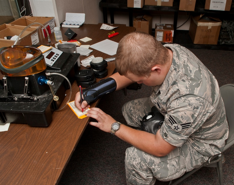 Senior Airman Zachary Hazuka, a central storage apprentice with the 5th Logistics Readiness Squadron, writes down the serial number for a chemical protection mask at Minot Air Force Base, N.D., Sept. 6, 2016. Hazuka keeps track of serial numbers for the gas mask tester on a spreadsheet in order to maintain accountability for each item. (U.S. Air Force photo/Airman 1st Class Jonathan McElderry)