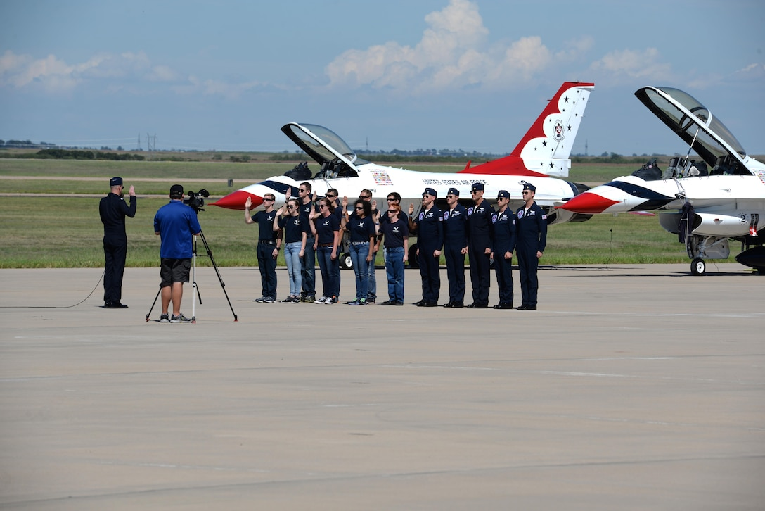The U.S. Air Force Thunderbirds stand beside future Airmen as they enlist during the Sheppard Air Force Base, Texas, Open House and Air Show, Sept. 17, 2016. The Thunderbirds are the Air Force's demonstration team that showcase the decisive combat power, precision and professionalism of the aviators, maintenance and support Airmen, placing emphasis on recruiting and building public trust and support for the Air Force's mission. (U.S. Air Force photo by Senior Airman Kyle E. Gese)