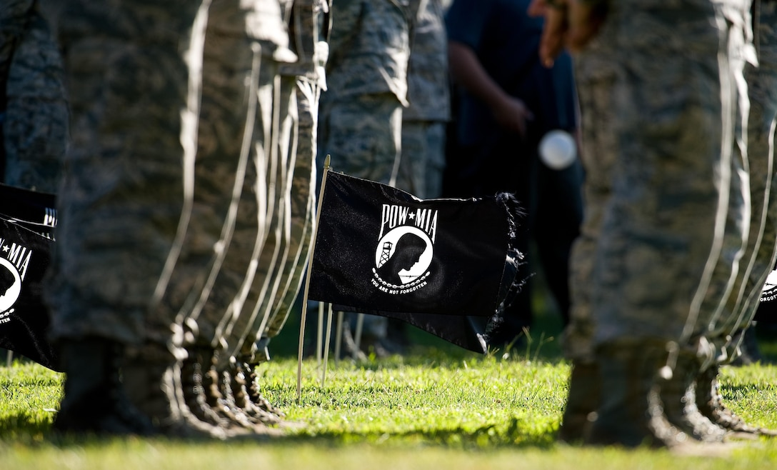 Twenty POW/MIA flags wave in a steady breeze during a retreat ceremony commemorating National POW/MIA Recognition Day Sept. 16, 2016, on Dover Air Force Base, Del. The 20 flags symbolized a flight made up of POW/MIA personnel and was placed between two Team Dover 20-man flights, making up the formation led by Col. Scott Gaab, 436th Airlift Wing vice commander. (U.S. Air Force photo by Roland Balik)