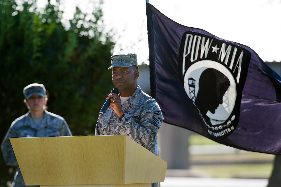 Retired Chief Master Sgt. Larence Kirby speaks to Team Dover members and guests during a retreat ceremony commemorating National POW/MIA Recognition Day Sept. 16, 2016, on Dover Air Force Base, Del. More than 130 fallen service members from previous wars and conflicts have been repatriated this past year. (U.S. Air Force photo by Roland Balik)