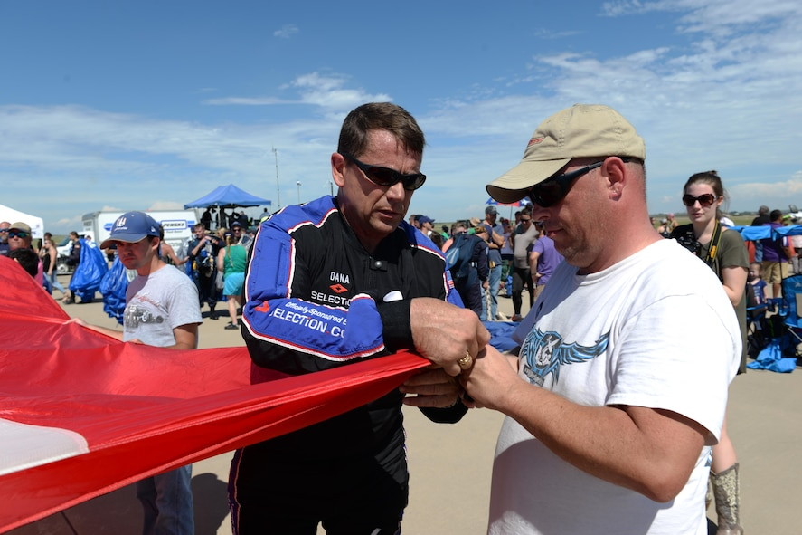 Dana Bowman, retired sergeant first class with the U.S. Army and well-renowned skydiver, folds his demonstration flag with Tony Gese, skydiving enthusiast, during the Sheppard Air Force Base, Texas, 75th Anniversary Air Show, Sept. 17, 2016. Bowman and the Wings of Blue team opened the 75th Anniversary Air Show Celebration. (U.S. Air Force photo by Senior Airman Kyle E. Gese)
