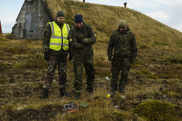 German military observers look at the remaining components of a detonated improvised explosive device during the Northern Challenge 16 exercise at Icelandic Coast Guard Keflavik Facility, Iceland, Sept. 19, 2016. During the exercise, 52nd EOD Airmen worked side by side with counterparts from allied and partner nations to become familiar with each other's military procedures and achieve greater interoperability in combating terrorism. (U.S. Air Force photo by Staff Sgt. Jonathan Snyder)
