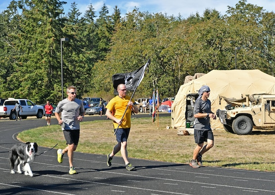 Capt. Joseph Hale, middle, and Bruce Robie, left, from the Western Air Defense Sector run in the POW/MIA Remembrance 24 Hour Run on Joint Base Lewis-McChord Sept. 14 to 15.  The event was hosted by the Air Force Sergeants Association and included participants from 24 Air Force teams from the active duty, Guard, and Reserves assigned to JBLM.  The WADS team members logged 1,037 laps for a total of 259 miles to raise awareness of the missing or imprisoned military service members. (U.S. Air National Guard photo by Kimberly D. Burke)