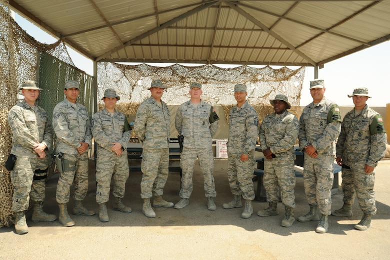 Members of the 387th Air Expeditionary Group force protection flight, civil engineering flight and security forces squadron come together for a group photo at an undisclosed location in Southwest Asia. The units worked together with little to no time off to build a new access road in less than 28 days for the busiest aerial port of debarkation in U.S. Air Forces Central Command. (U.S. Air Force photo/Senior Airman Zachary Kee)