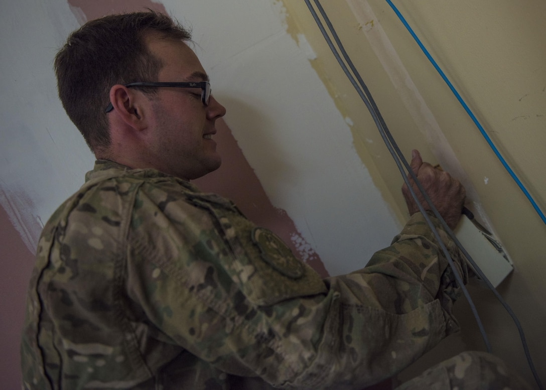 Senior Airman John Roach, 455th Expeditionary Communications Squadron, cable and antenna maintenance journeyman, pulls off a cable box, Bagram Airfield, Afghanistan, Sept. 20, 2016. The 455th ECS and 455th Expeditionary Civil Engineer Squadron are building new walls and replacing communication cables for a new office. (U.S. Air Force photo by Senior Airman Justyn M. Freeman)