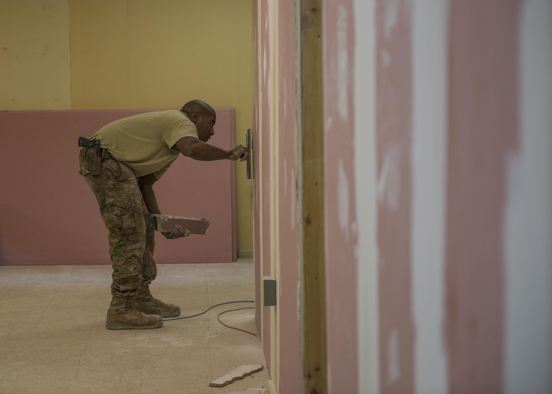 Staff Sgt. Donald Scott, 455th Expeditionary Civil Engineer Squadron structures, applies joint compound which helps seal joints between drywall, Bagram Airfield, Afghanistan, Sept. 20, 2016. The structures team paired with the 455th ECS to renovate and provide communications for the building. (U.S. Air Force photo by Senior Airman Justyn M. Freeman)