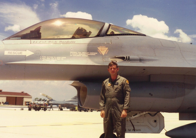 Retired Lt. Col. Richard Burdette poses for a photo with his F-16 Fighting Falcon at MacDill Air Force Base, Fla., in 1990.  According to him, the best pilot from the three generations in his family was his father.  His father, 2nd Lt. Harry Burdette, flew an unpressurized B-17 Flying Fortress above 30,000 feet and had to wear a flight suit plugged into the aircraft's electrical system for warmth while assigned to the 379th Bombardment Group during World War II. (Courtesy photo/Richard Burdette/Released)