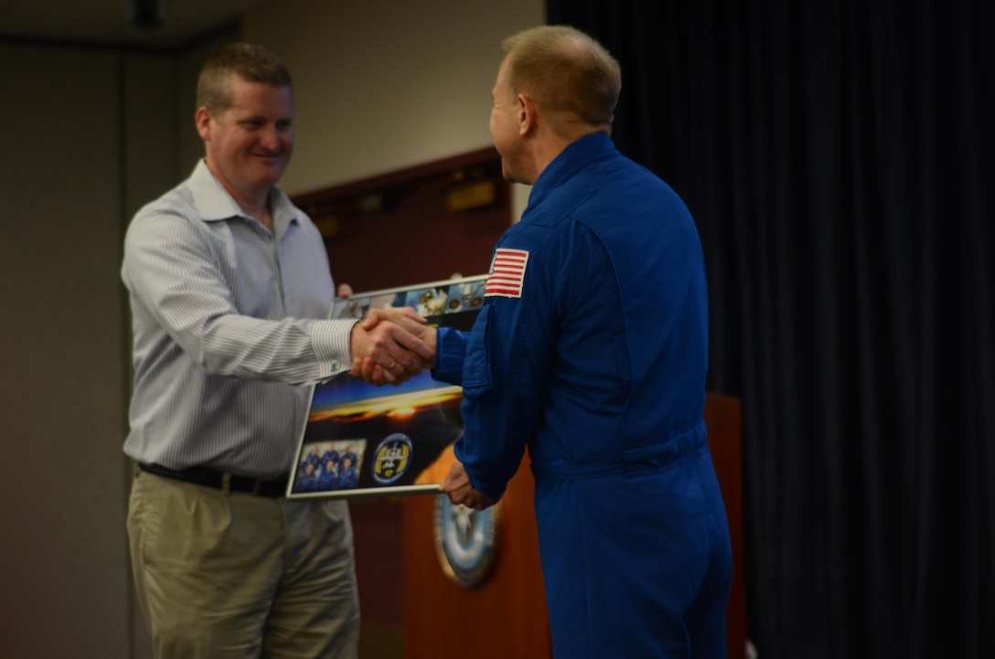 Joseph A. Coslett (left), the public affairs officer for the Defense Information School , receives a gift from NASA astronaut Timothy L. Kopra after Kopra detailed his experience with Expeditions 46 and 47, which went to the International Space Station from March 2, 2016, until June 18, 2016. Kopra was the commander of Expedition 47, and his stop at DINFOS is part of his post-flight tour. (Photo by Army Cpl. Matthew Atwood)