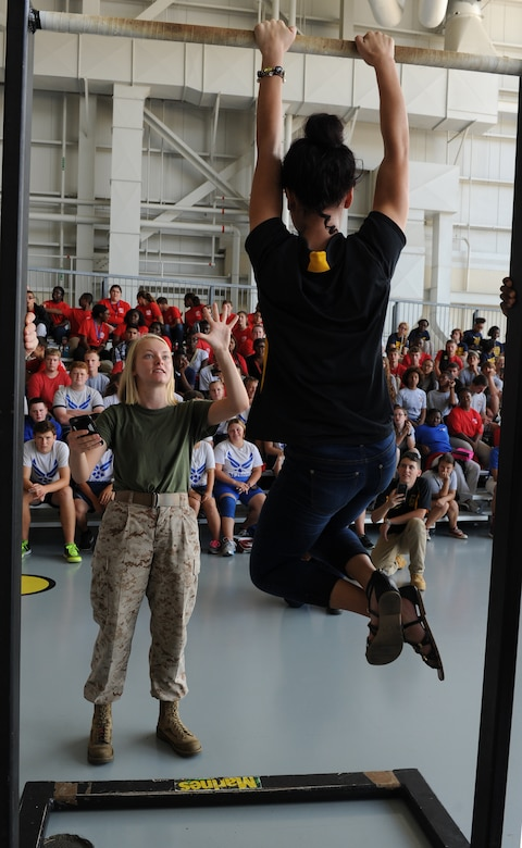 U.S. Marine Lance Cpl. Sarah Tedford, Keesler Marine Detachment student, shows Elizabeth Zelaya, D'Iberville High School Junior ROTC student, her remaining time to hang on the pull-up bar during a pull-up competition at the Science, Technology, Engineering and Mathematics Diversity Outreach Day in the fuel cell hangar Sept. 16, 2016 on Keesler Air Force Base, Miss. The event also consisted of nine Mississippi gulf coast high school Junior ROTC units and science students viewing an 81st Security Forces Squadron military working dog demonstration and visiting informative booths about Air Force opportunities and accession requirements with an emphasis on STEM. (U.S. Air Force photo by Kemberly Groue/Released)