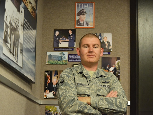 Staff Sgt. Ryan Reavis, 50th Operations Support Squadron, stands in front of a display of pictures and magazine articles depicting important moments in Schriever's history in the 50th Space Wing Heritage room at Schriever Air Force Base, Colorado, Friday, Sept. 16, 2016. Reavis himself made history for the base when he was selected to be among the first enlisted Airmen to be formally trained as pilots since World War II. (U.S. Air Force photo/Airman William Tracy)