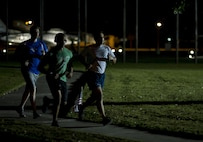 (Left to right) U.S. Air Force Senior Airmen Dustin Mullen and Ty-Rico Lea, and Tech. Sgt. Javier Cruz from the 325th Fighter Wing Public Affairs Office participate in the Prisoner of War/Missing in Action Memorial 24 Hour Vigil Run at Flag Park, Tyndall Air Force Base, Fla., Sept. 16, 2016. The public affairs team ran for two hours, from midnight to 2 a.m., during the memorial event. (U.S. Air Force photo by Staff Sgt. Alex Fox Echols III/Released)