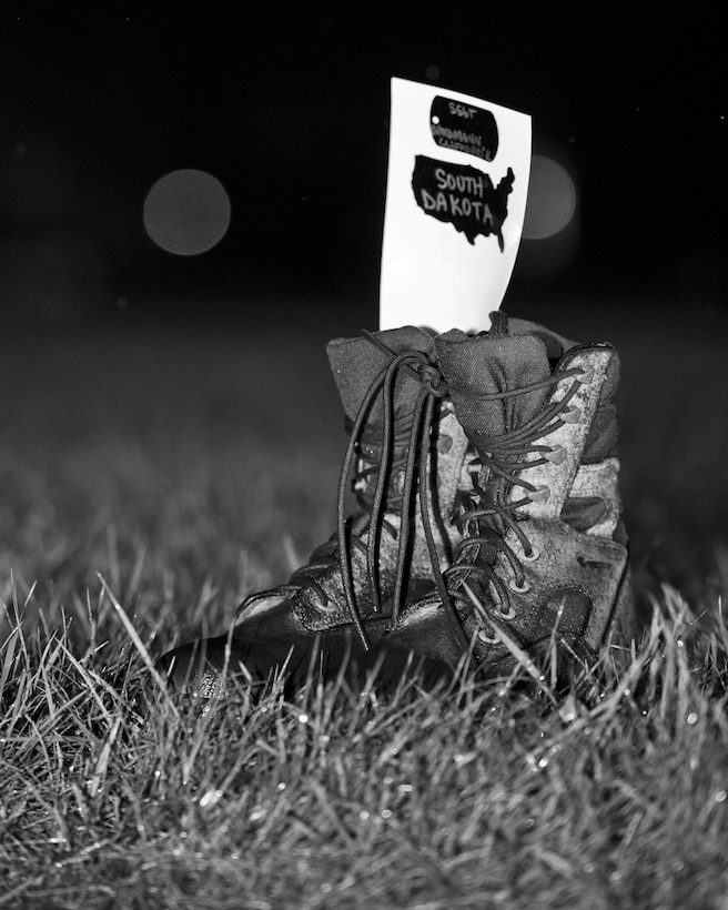 Combat boots line the outdoor track in the rain at Minot Air Force Base, N.D., Sept. 15, 2016. The boots symbolized prisoners of war and missing in action service members during a POW/MIA memorial event. (Airman 1st Class J.T. Armstrong)