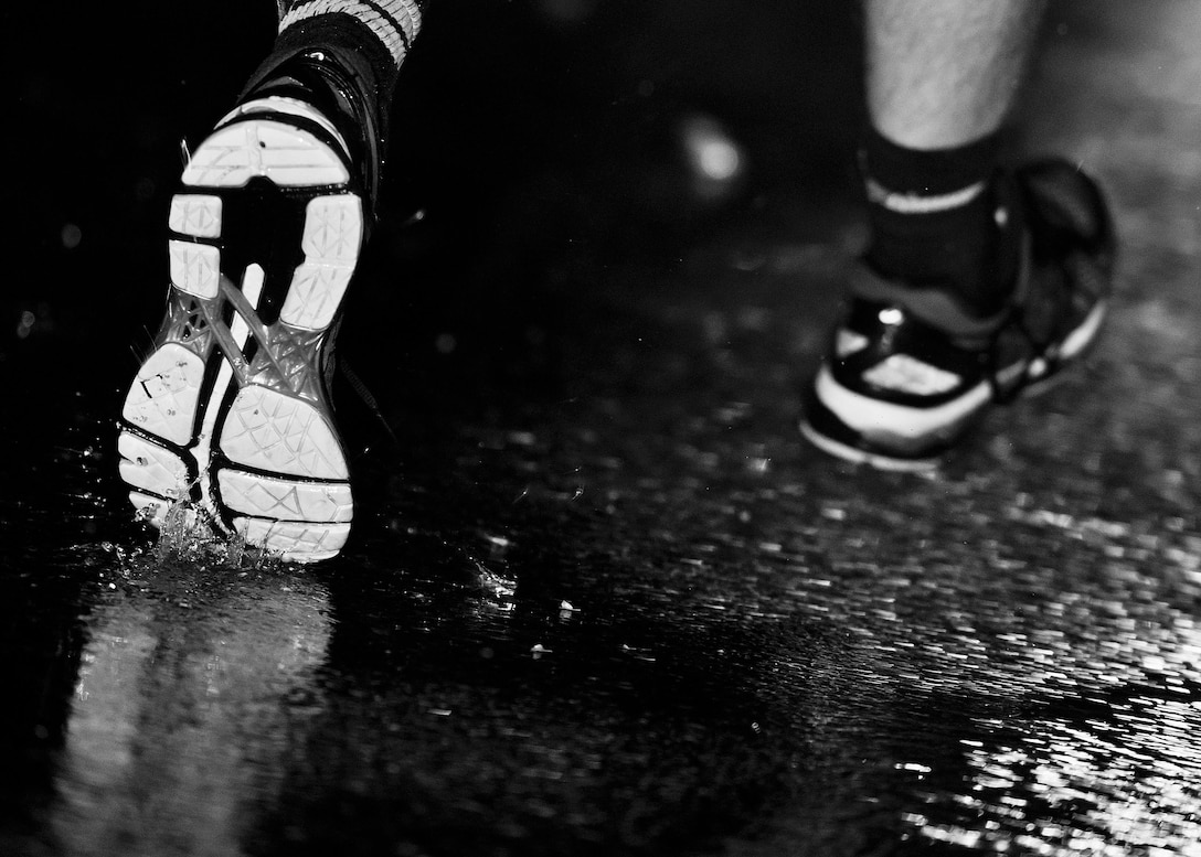 An Airman's shoes splash through the puddles around the outdoor track at Minot Air Force Base, N.D., Sept. 15, 2016. Airmen from across both wings ran the Prisoners of War/Missing in Action flag around the outdoor track for 24 hours in honor of those who are lost but not forgotten. (Airman 1st Class J.T. Armstrong)