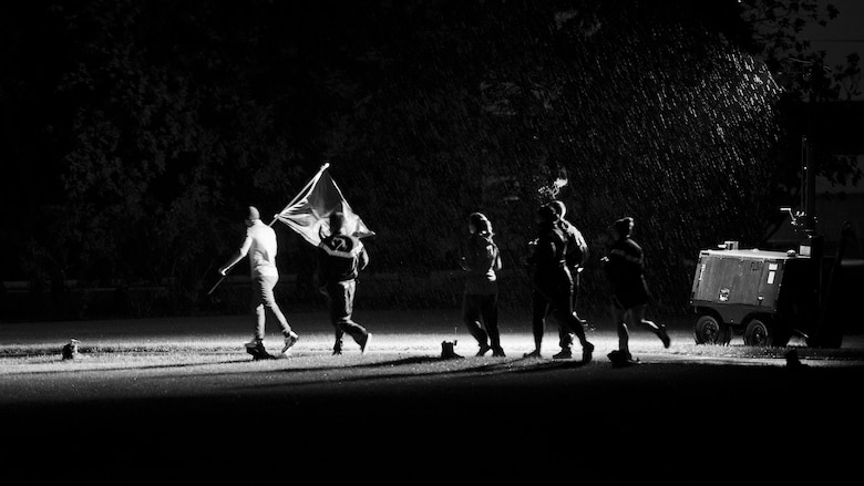 A group of Team Minot Airmen run through the rain during a memorial event at Minot Air Force Base, N.D., Sept. 15, 2016. Throughout the night Airmen traded off carrying the Prisoners of War/Missing in Action flag around the outdoor track. (Airman 1st Class J.T. Armstrong)