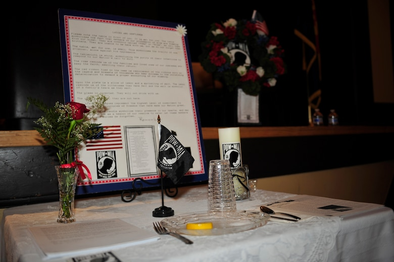 A table set for one stays vacant during a POW/MIA recognition ceremony at the main veteran's affairs campus R.E. Lindsay Auditorium in Tucson, Ariz., Sept. 16, 2016. The table cloth symbolizes the purity of their intentions, the rose of the families and loved ones who await their return, the red ribbon shows the determination to demand proper accounting for those missing, the lemon is symbolic of the bitterness they faced and the salt represents the tears of their loved ones. Finally the inverted glass and empty chair and to show that they are still missing. (U.S. Air Force photo by Senior Airman Cheyenne A. Powers)
