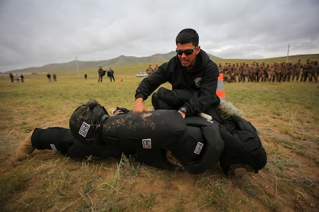 U.S. Marine Cpl. Ezequiel Silva, a military police Marine with 3rd Law Enforcement Battalion, III Marine Expeditionary Force, demonstrates a mechanical advantage control holds technique during Non-Lethal Weapons Executive Seminar (NOLES) 2016 at the Five Hills Training Area, Mongolia, Sept. 17, 2016. Mongolian soldiers and National Police were exposed to oleoresin capsicum spray and had to complete a five-level circuit course. Non-lethal weapons are designed to incapacitate equipment and personnel while minimizing fatalities and permanent injury to personnel, and undesired collateral damage to property.  (U.S. Marine Corps photo by Cpl. Jonathan E. LopezCruet)