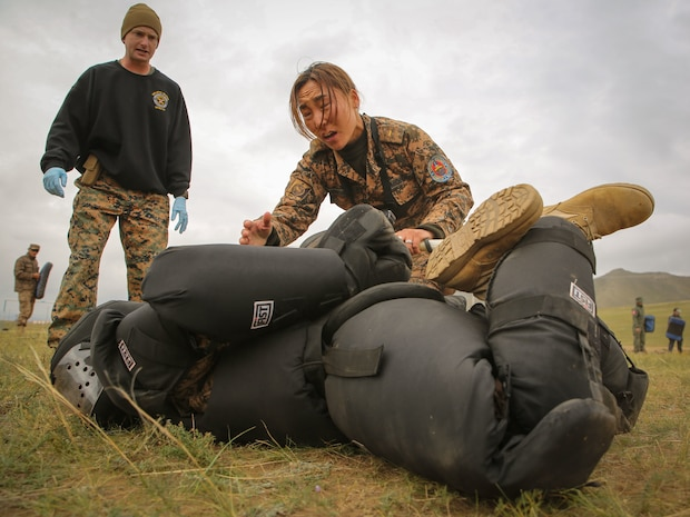 Mongolian Armed Forces Junior Sgt. Battsend Enkhtuya executes a mechanical advantage control holds technique after being sprayed with oleoresin capsicum during Non-Lethal Weapons Executive Seminar (NOLES) 2016 at the Five Hills Training Area, Mongolia, Sept. 17, 2016. Mongolian soldiers and National Police were exposed to Oleoresin Capsicum (OC) spray. Mongolian soldiers and National Police were exposed to oleoresin capsicum spray and had to complete a five-level circuit course. Non-lethal weapons are designed to incapacitate equipment and personnel while minimizing fatalities and permanent injury to personnel, and undesired collateral damage to property.