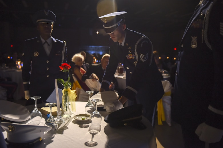 U.S. Air Force Tech. Sgt. James Pennington, Goodfellow Air Force Base Honor Guard NCO in charge, places a service cap on a POW/MIA table during Goodfellow Air Force Base's Annual Air Force Ball at the McNease Convention Center, San Angelo, Texas, Sept. 16, 2016. The POW/MIA table honored missing and captured service members. (U.S. Air Force photo by Airman 1st Class Chase Sousa/Released)
