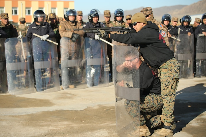 U.S. Marine Cpl. Ezequiel Silva and Cpl. Samuel Masse, both military police Marines with 3rd Law Enforcement Battalion, III Marine Expeditionary Force, demonstrate proper use of non-lethal weapons during the riot control portion Non-Lethal Executive Seminar (NOLES) 2016 at Five Hills Training Area, Mongolia, Sept. 20, 2016. Mongolian soldiers and National Police completed the final portion of the field training exercise for NOLES with a riot control situation. Non-lethal weapons are designed to incapacitate equipment and personnel while minimizing fatalities and permanent injury to personnel, and undesired collateral damage to property. (U.S. Marine Corps photo by Cpl. Jonathan E. LopezCruet)