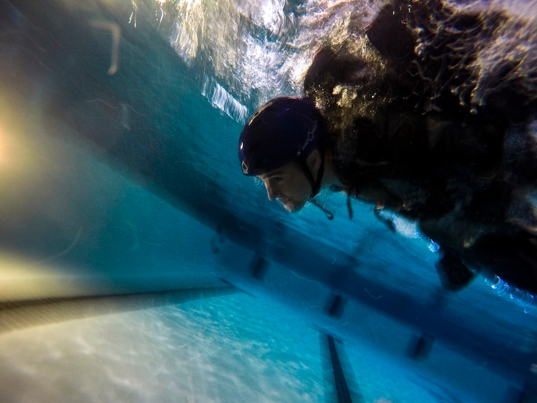 U.S. Air Force Senior Master Sgt. Scott Shier, 71st Rescue Squadron loadmaster, swims during a parachute line scenario during water survival training, Sept. 15, 2016, at Moody Air Force Base, Ga. Survival, Evasion, resistance and escape specialists from the 347th Operations Support Squadron are responsible for familiarizing aircrews with survival equipment and proper techniques to survive in water in the event of ejecting from an aircraft. (U.S. Air Force photo by Airman 1st Class Daniel Snider)