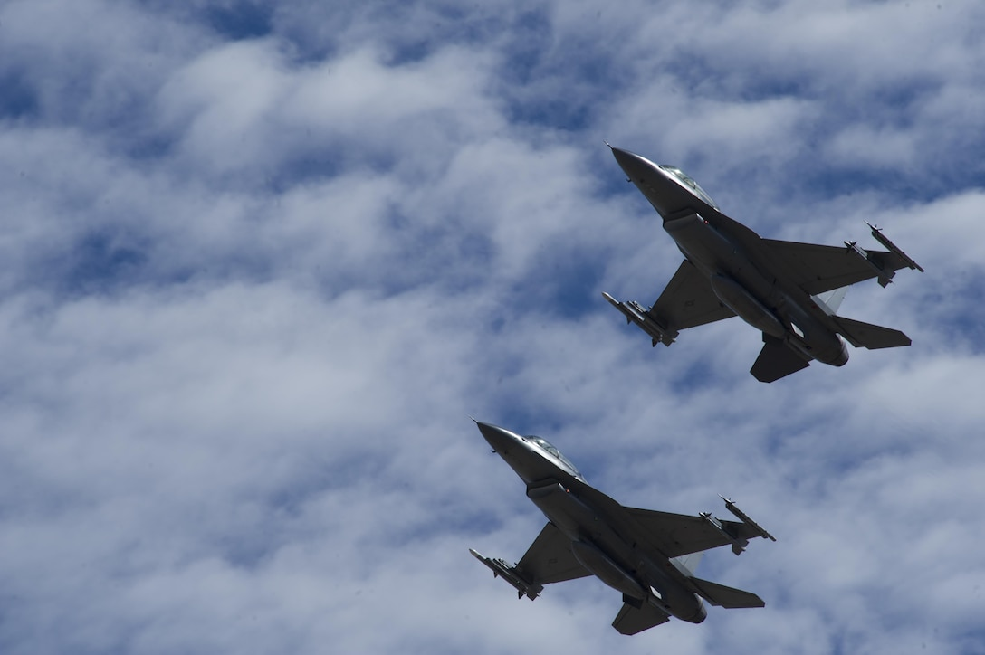 Two F-16 Fighting Falcons fly in formation over Holloman Air Force Base, N.M. on Sept. 13, 2016, in front of 160 spectators participating in Holloman's annual Phantom Society Tour. The tour enabled aircraft enthusiasts, including veterans and non-veterans with aviation backgrounds, to learn more about Holloman AFB's aircraft and mission. The tour included an F-16 Fighting Falcon static display and briefing, travel to Holloman's High Speed Test Track, the opportunity to view QF-4 Phantom IIs and F-16s in flight, and a visit to the base's heritage park to view static displays of various aircraft historically stationed at Holloman AFB. (U.S. Air Force photo by Master Sgt. Matthew McGovern)