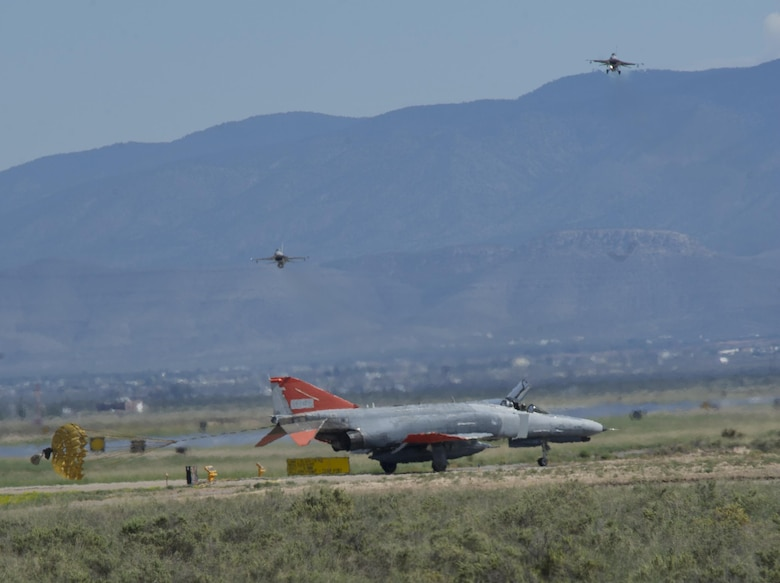 A QF-4 Phantom II taxis after arrival to Holloman Air Force Base, N.M., on Sept. 13, 2016, while two F-16 Fighting Falcons depart in front of 160 spectators participating in Holloman's annual Phantom Society Tour. The tour enabled aircraft enthusiasts, including veterans and non-veterans with aviation backgrounds, to explore various base locations. The tour also included an F-16 Fighting Falcon static display and briefing, travel to Holloman's High Speed Test Track, the opportunity to view QF-4 Phantom IIs and F-16s in flight, and a visit to the base's heritage park to view static displays of various aircraft historically stationed at Holloman AFB. (U.S. Air Force photo by Master Sgt. Matthew McGovern)